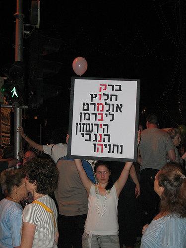 """הח""""מ בהפגנה נגד ממשלת אולמרט-ברק אחרי מלחמת לבנון השנייה, 2006. רק בדיעבד הבנתי למה כ""""כ הרבה אנשים כעסו שהכנסתי גם את נתניהו לשלט שהכנתי."""